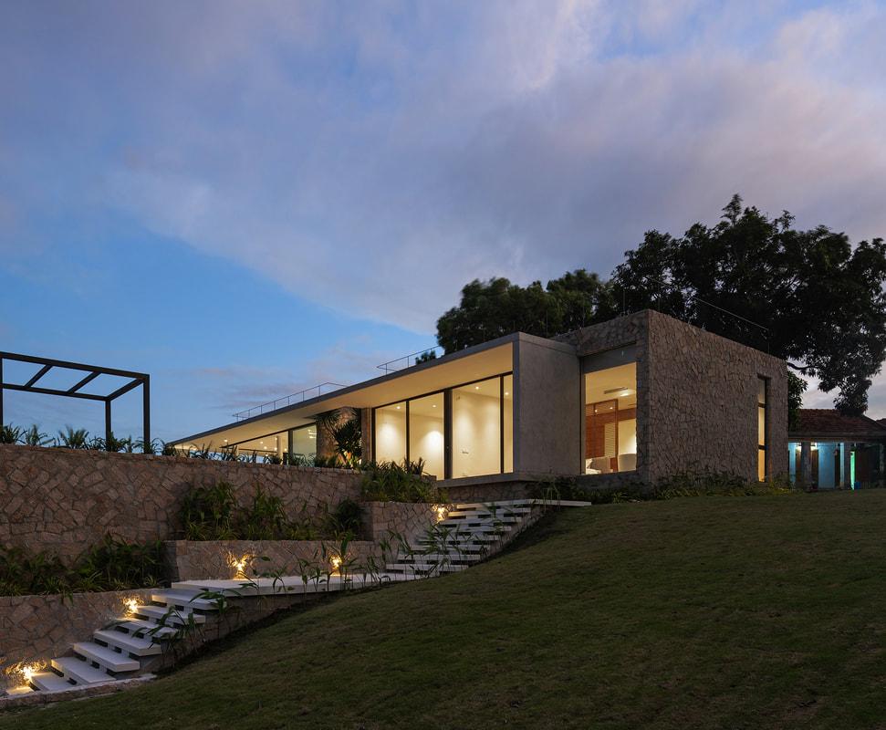 Hình ảnh một góc ngôi nhà trên đồi khi đêm xuống với ánh đèn vàng rực rỡ, ấm áp