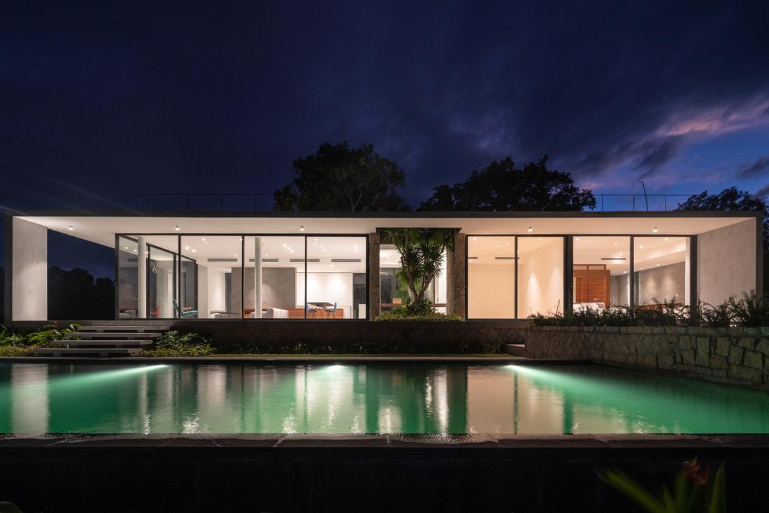 Hình ảnh cận cảnh mặt tiền công trình rực sáng khi đêm xuống, phía trước là hồ bơi trong xanh, sử dụng đèn hắt