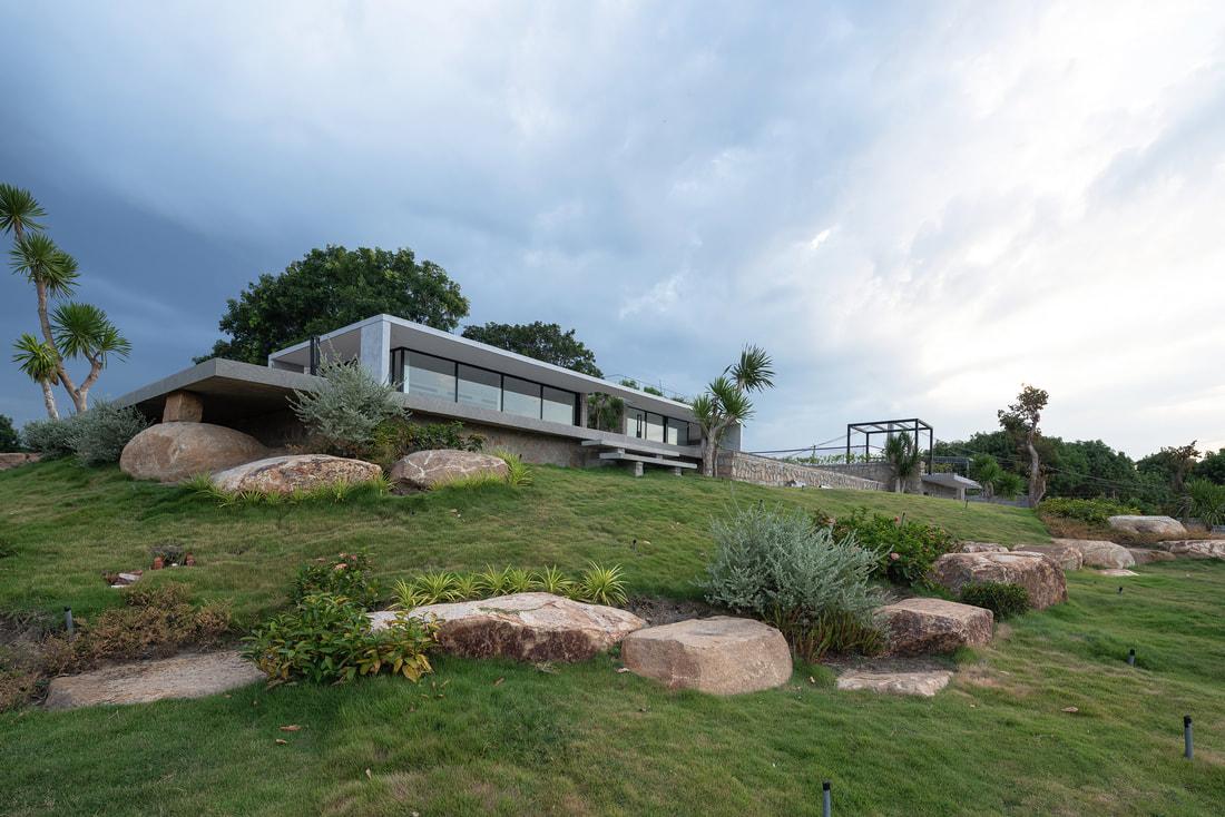 Hình ảnh toàn cảnh mặt tiền nhà trên đồi đá với cửa kính trong suốt, những khối đá lớn bao quanh
