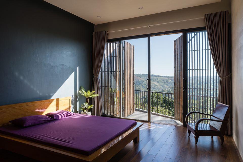 Phòng ngủ trong nhà Gia Nghĩa nổi bật với ga giường màu tím, ghế gỗ thư giãn, cửa lớn mở ra ban công