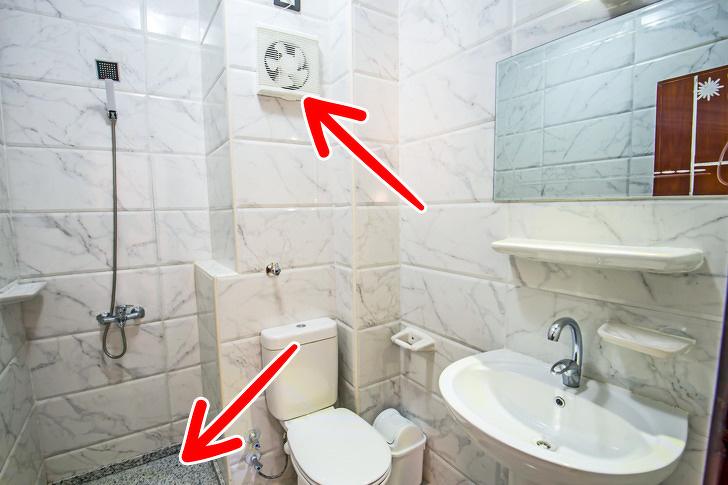 Hình ảnh bên trong một phòng vệ sinh tôn màu trắng chủ đạo, được trang bị quạt thông gió, chống thấm tốt.