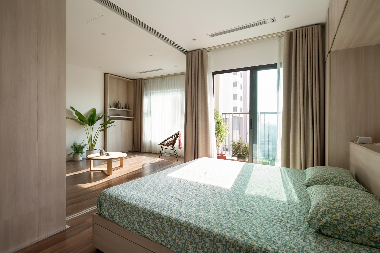 Hình ảnh phòng ngủ đơn giản với ga gối màu xanh họa tiết hoa, cửa sổ kính lớn