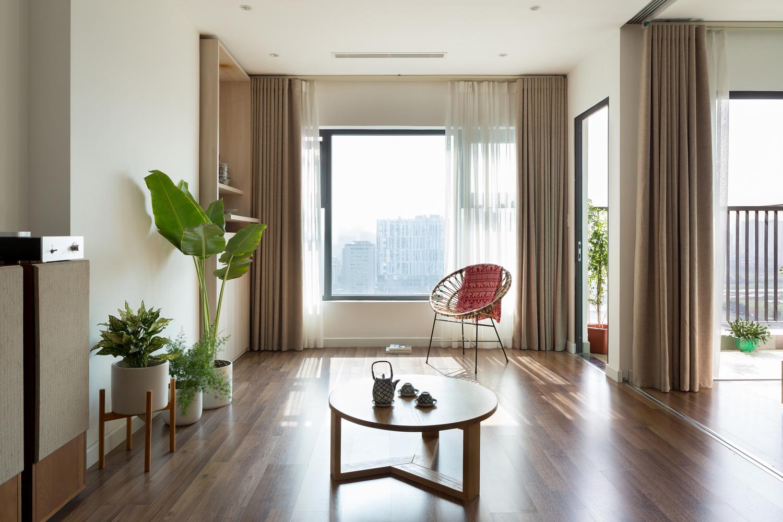 Không gian phòng khách có thiết kế tối giản với bàn trà gỗ hình tròn nhỏ xinh đặt ở trung tâm. Cạnh khung cửa sổ kính lớn là ghế ngồi thư giãn, đọc sách.