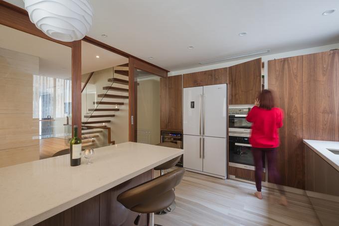 Hình ảnh người phụ nữ trẻ tuổi mặc áo hồng di chuyển trong phòng bếp