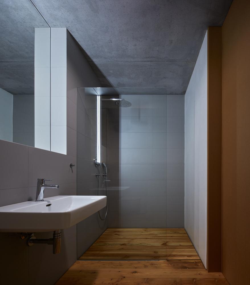 Hình ảnh bên trong phòng vệ sinh với tường, trần màu xám bê tông, buồng tắm đứng, vách ngăn kính trong suốt