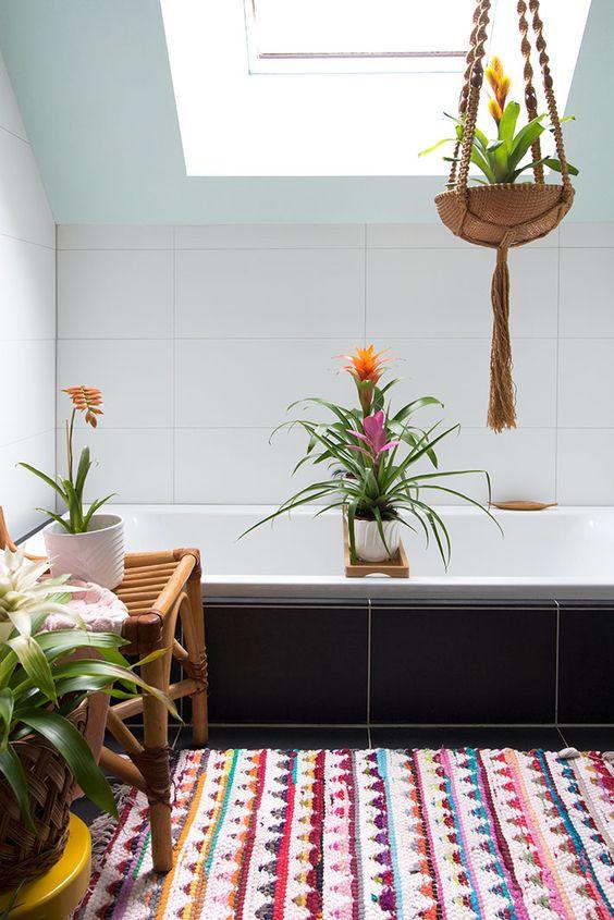 Hình ảnh bên trong phòng tắm hiện đại được trang trí bởi cây dứa cảnh, thảm trải sàn họa tiết thổ cẩm bắt mắt