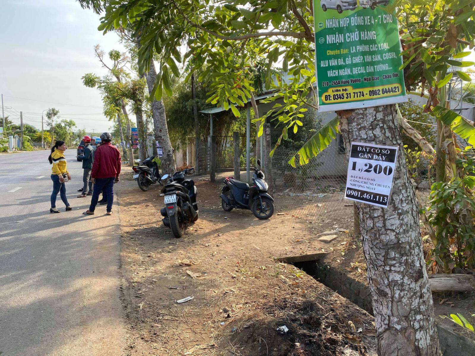 Một con đường ở xã Bình Ba, vài người đứng trao đổi, biển rao bán đất treo trên cây.