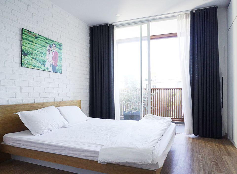 Cận cảnh bên trong phòng ngủ với tường, trần màu trắng, giường gỗ, rèm cửa màu xám đen