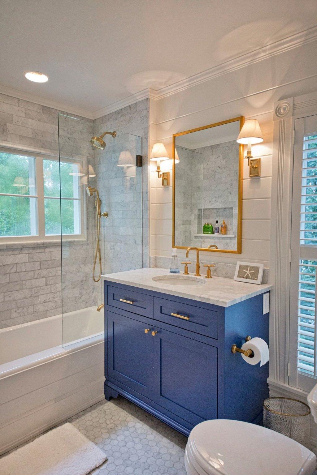 Ảnh chụp một góc phòng tắm với tủ ngăn kéo màu xanh dương, khung gương vàng đồng.