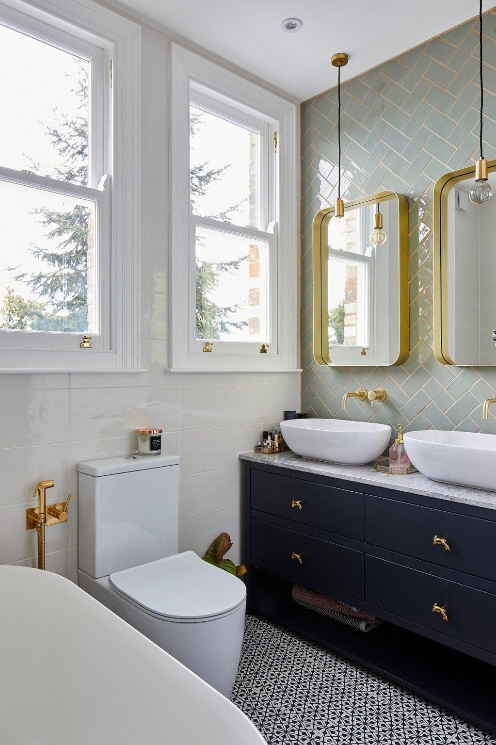 Hình ảnh một góc phòng tắm với tủ màu xám xanh đậm, gương khung viền màu đồng, cửa sổ kính