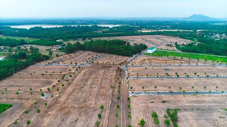Hình ảnh một dự án đất nền nhìn từ trên cao, xung quanh nhiều cây xanh, lác đác nhà ở