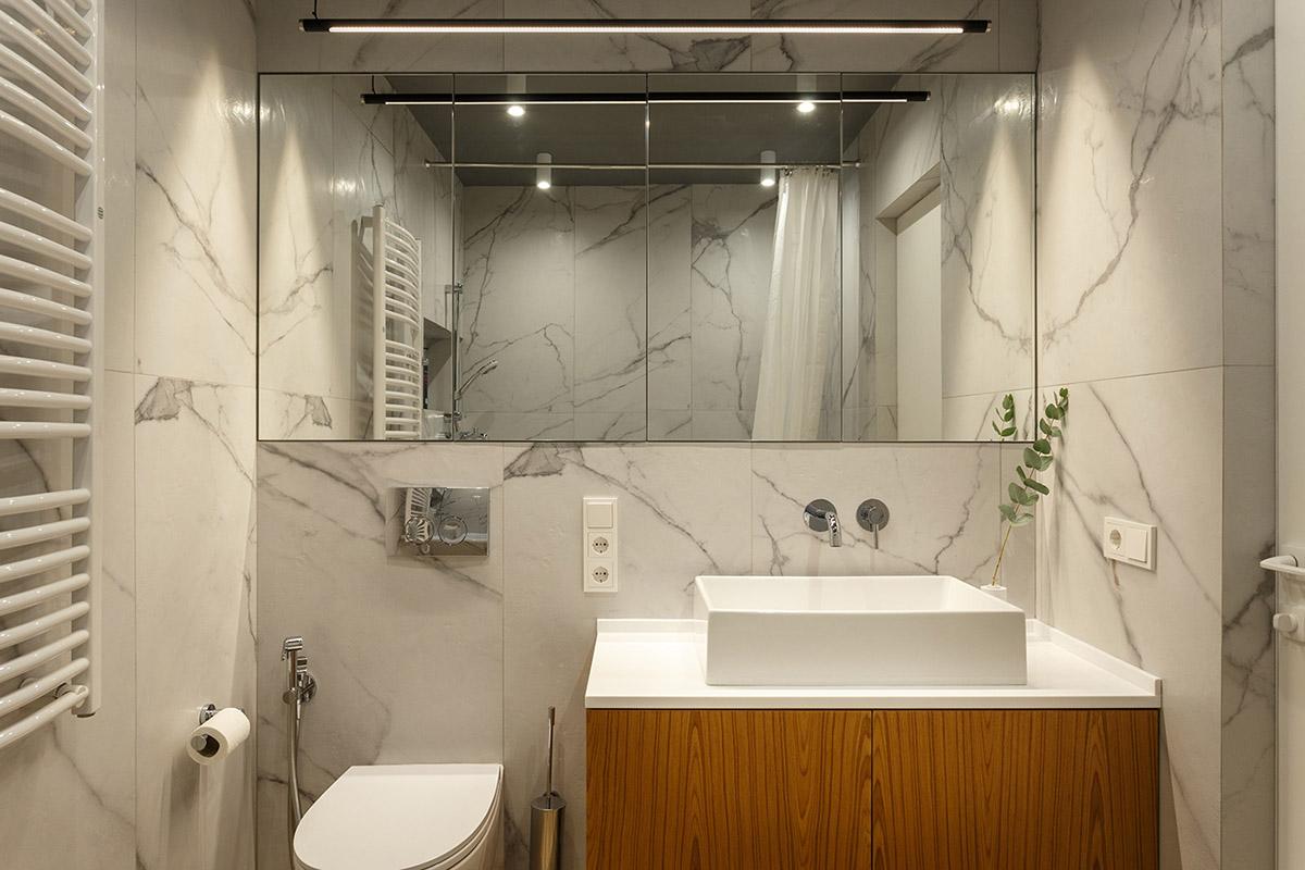 Hình ảnh một góc phòng vệ sinh với gương lớn, đá cẩm thạch ốp lát,