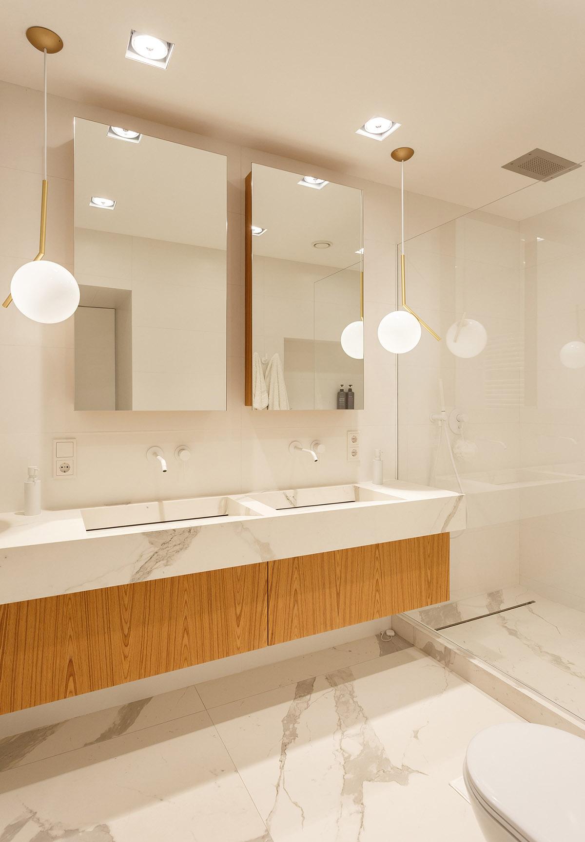 Hình ảnh phòng vệ sinh màu trắng chủ đạo được ốp lát đá cẩm thạch, sử dụng gương lướn, đèn thả mặt dây chuyền hình tròn bắt mắt.