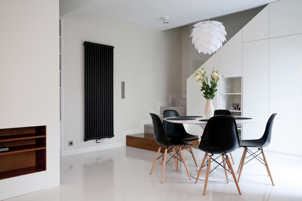 Hình ảnh phòng ăn gọn xinh đặt bên cạnh cửa sổ, nổi bật với ghế ngồi màu đen, đèn thả cá tính