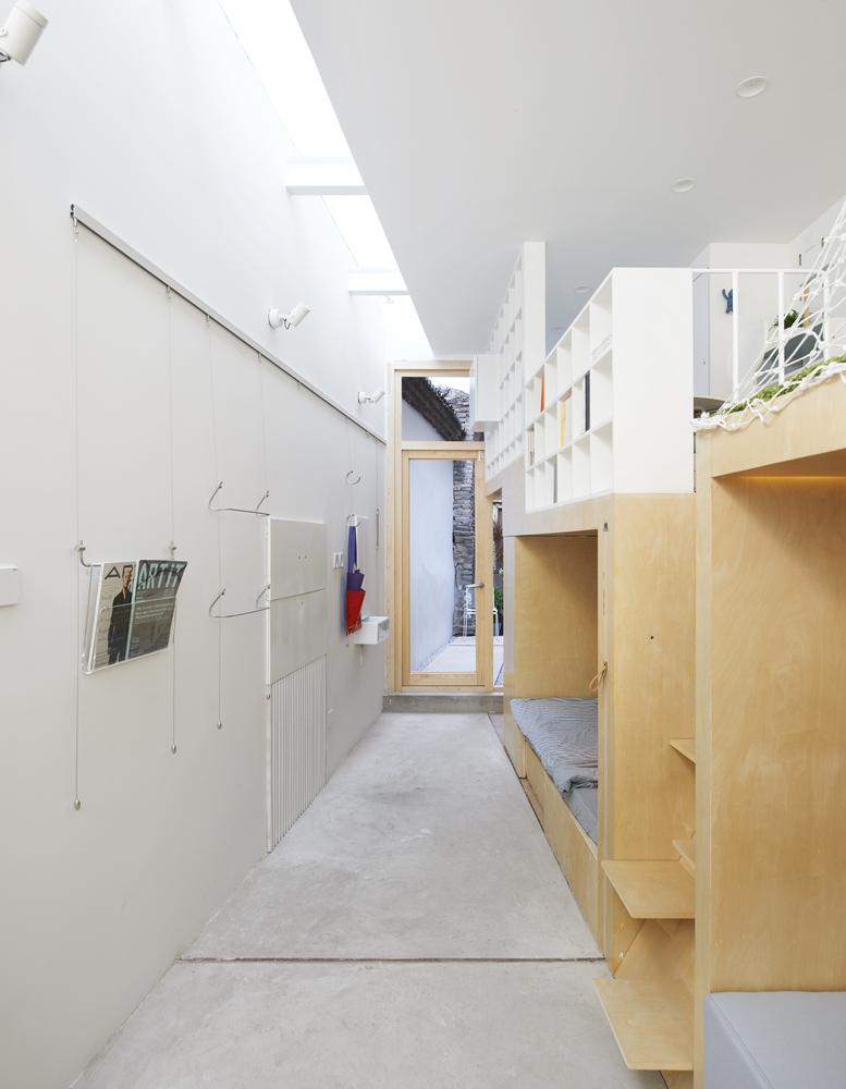 Cận cảnh không gian ngủ nghỉ trong các khối hộp gỗ, cạnh đó là bức tường trắng tinh khôi, khe lấy sáng trên mái.