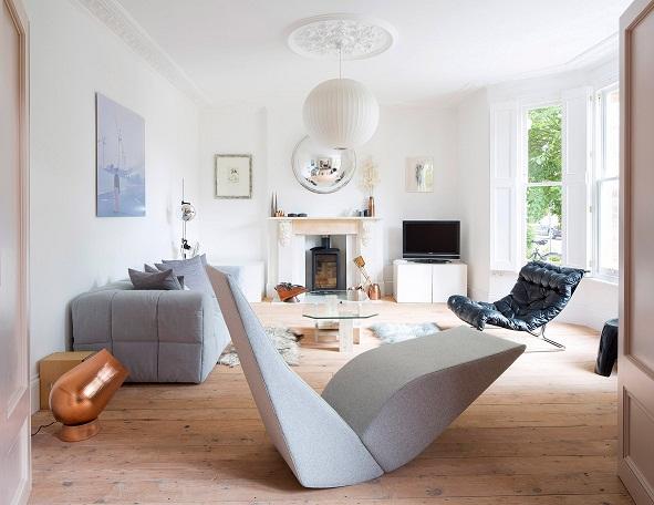 Hình ảnh toàn cảnh phòng khách rộng thoáng với sofa ghi xám, ghế da thư giãn, ghế bành độc đáo, trang trí bằng tranh treo tường
