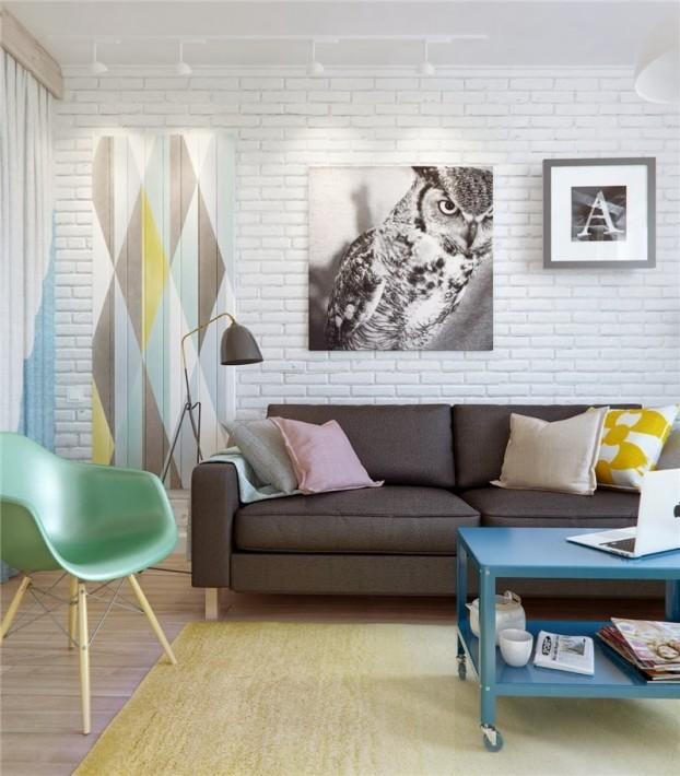 Hình ảnh một góc phòng khách với sofa màu nâu, phía trước đặt bàn trà xanh dương, cạnh đó là ghế tựa xanh lá, tranh chim cú treo tường.