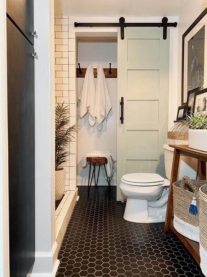 Hình ảnh bên trong một phòng tắm nhỏ với cửa trượt gỗ màu sáng phân tách giữa khu tắm và vệ sinh.