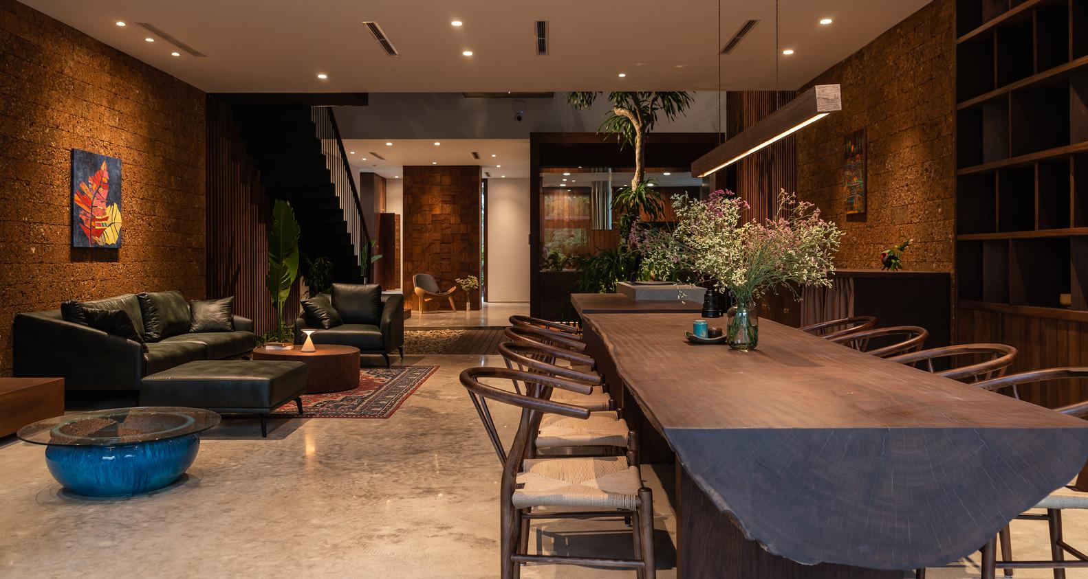 Hình ảnh phòng khách với tường gạch tổ ong, ghế sofa màu xanh lá, tranh treo tường màu sắc, cạnh đó là khu bếp ăn hiện đại