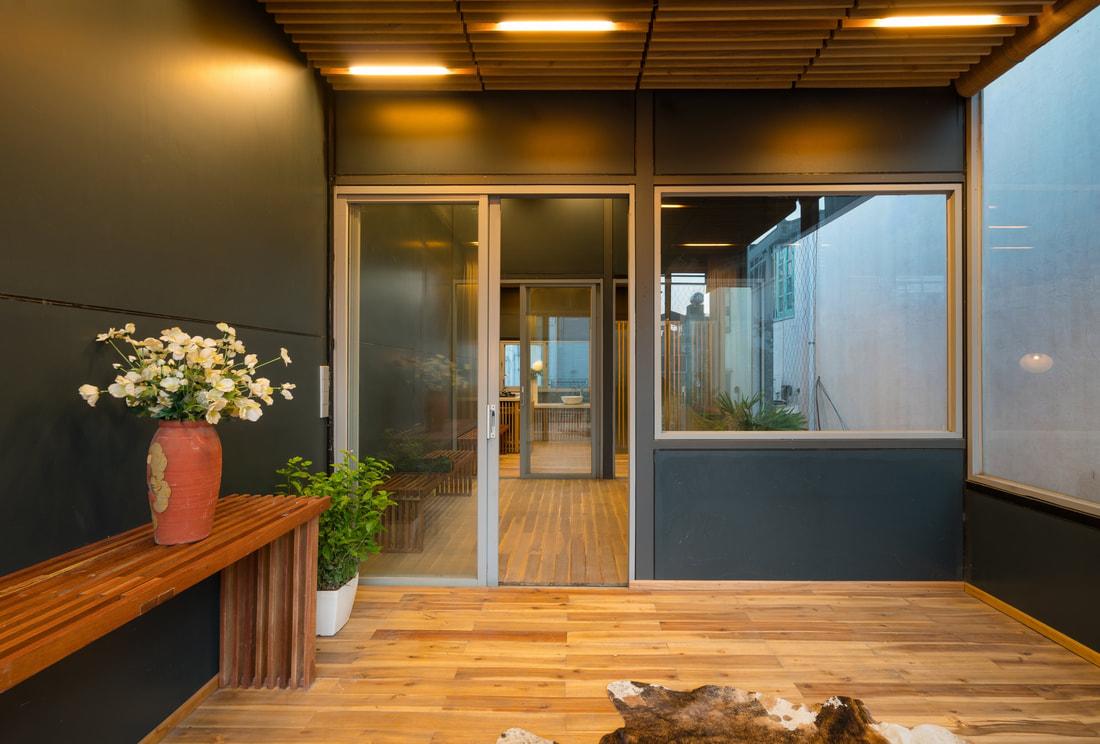 Hình ảnh cận cảnh bình hoa đặt trên kệ gỗ, bên cạnh là chậu cây xanh mướt trong căn phòng có tường màu xanh biển đậm