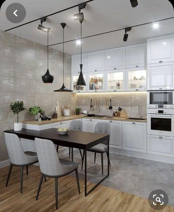 Hình ảnh toàn cảnh phòng bếp với hệ tủ màu trắng, bệ bếp kéo dài thành bàn ăn cho 4 người, đèn thả trần màu đen - trắng cá tính.