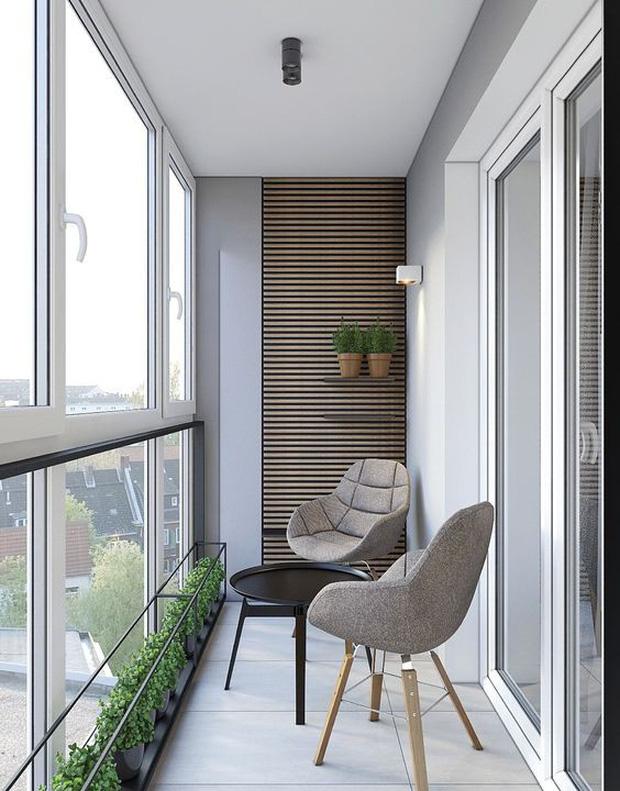Hình ảnh ban công nhà phố được bài trí thành góc đọc sách, uống trà với hai ghế tựa màu xám, bàn trà tròn màu đen, cửa kính cường lực trong suốt