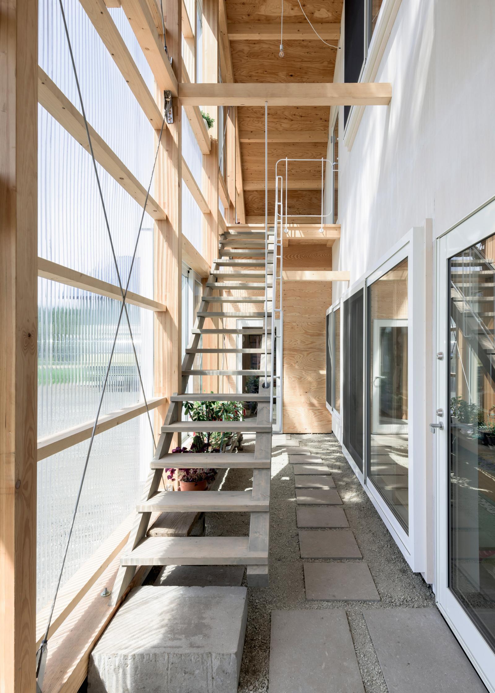 Hình ảnh cận cảnh cầu thang nhỏ bậc hở thông thoáng, xung quanh là các cấu trúc gỗ màu sáng.