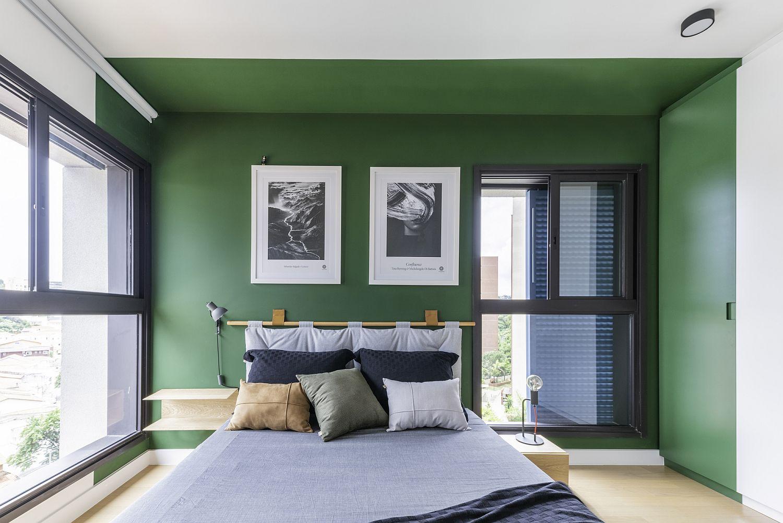 Hình ảnh phòng ngủ hiện đại với tường màu xanh lá, tranh treo đầu giường, cửa sổ kính lớn