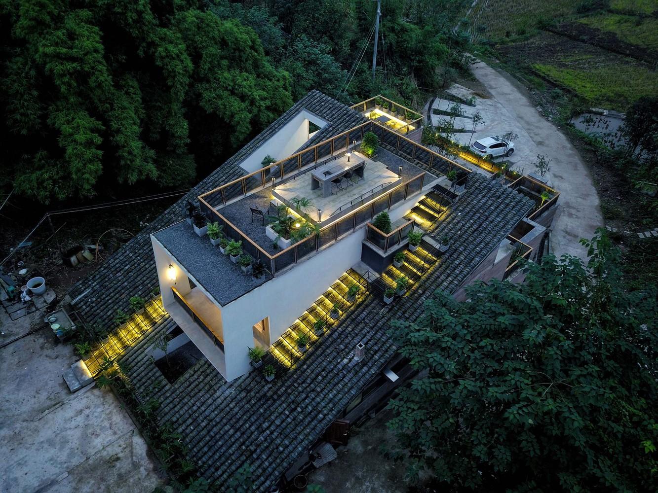 Ảnh chụp sân thượng từ trên cao với bàn ăn ngoài trời, nhiều chậu cây cảnh, đèn trang trí ấm áp.