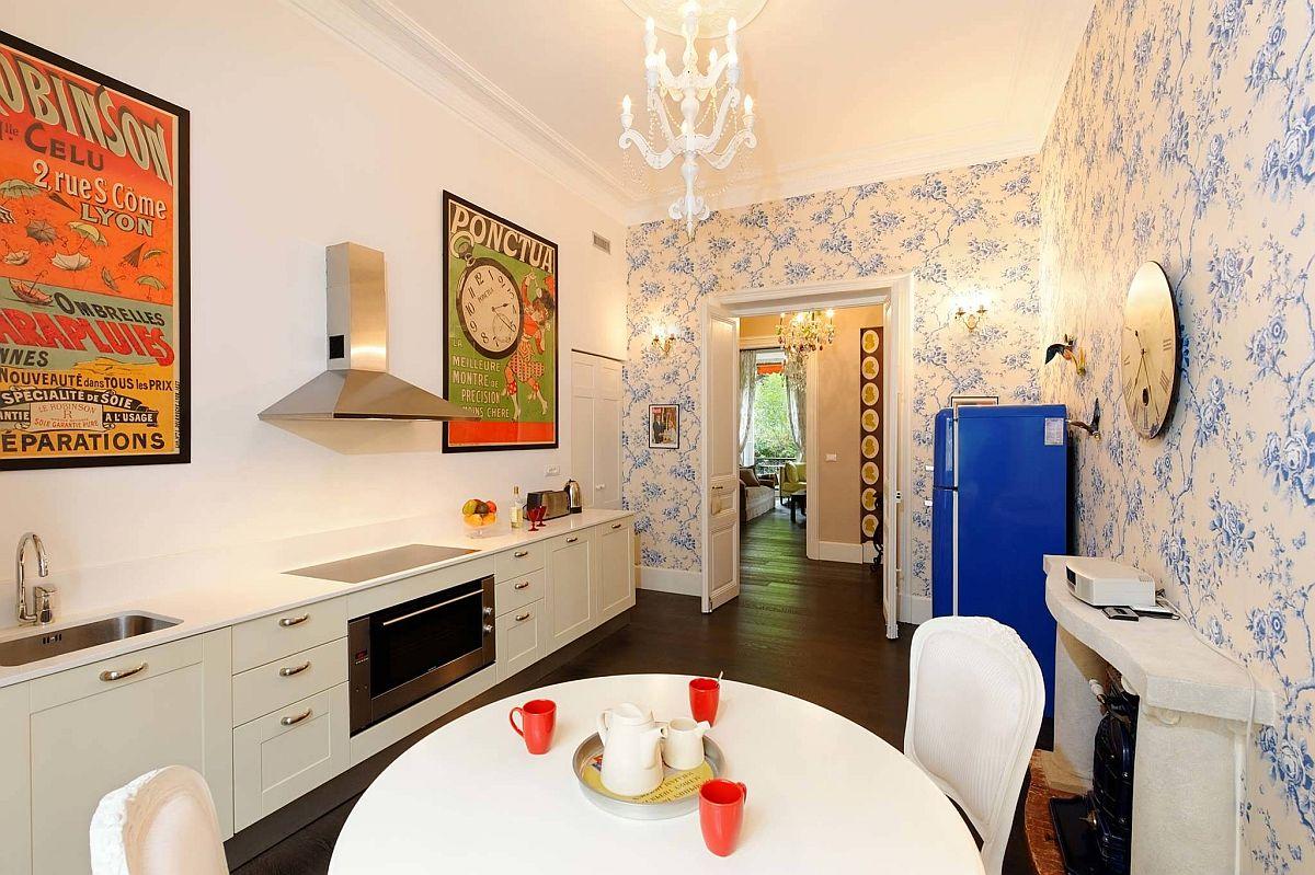 Hình ảnh toàn cảnh phòng bếp với giấy dán tường hoa văn màu xanh nhỏ nhẹ nhàng, tranh treo tường màu nóng ấm áp