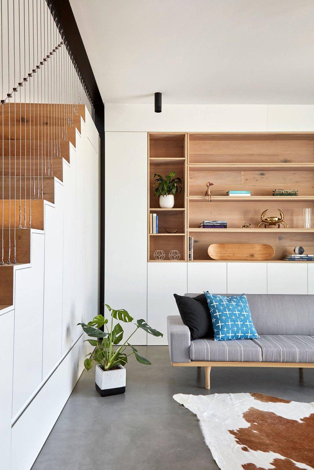 Hình ảnh một góc phòng khách màu trắng sử dụng kệ tủ gỗ lưu trữ, cạnh đó là cầu thang