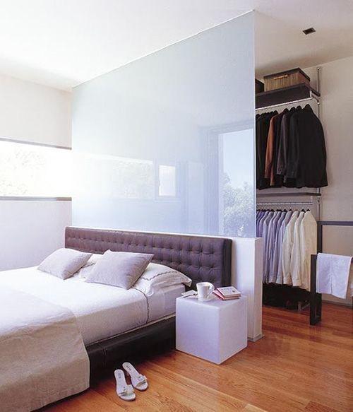 Hình ảnh cận cảnh một góc phòng ngủ với giường đặt cạnh cửa sổ, phía sau vách kính mờ là phòng thay đồ