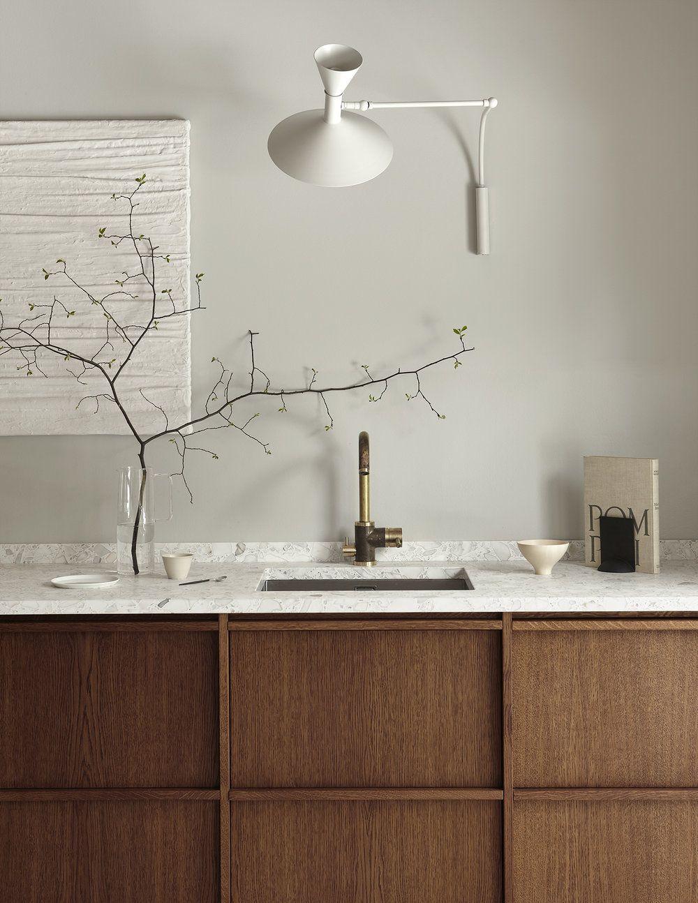 Hình ảnh một góc phòng bếp với bồn rửa bát, bề mặt ốp đá màu rắng, bình cây trang trí