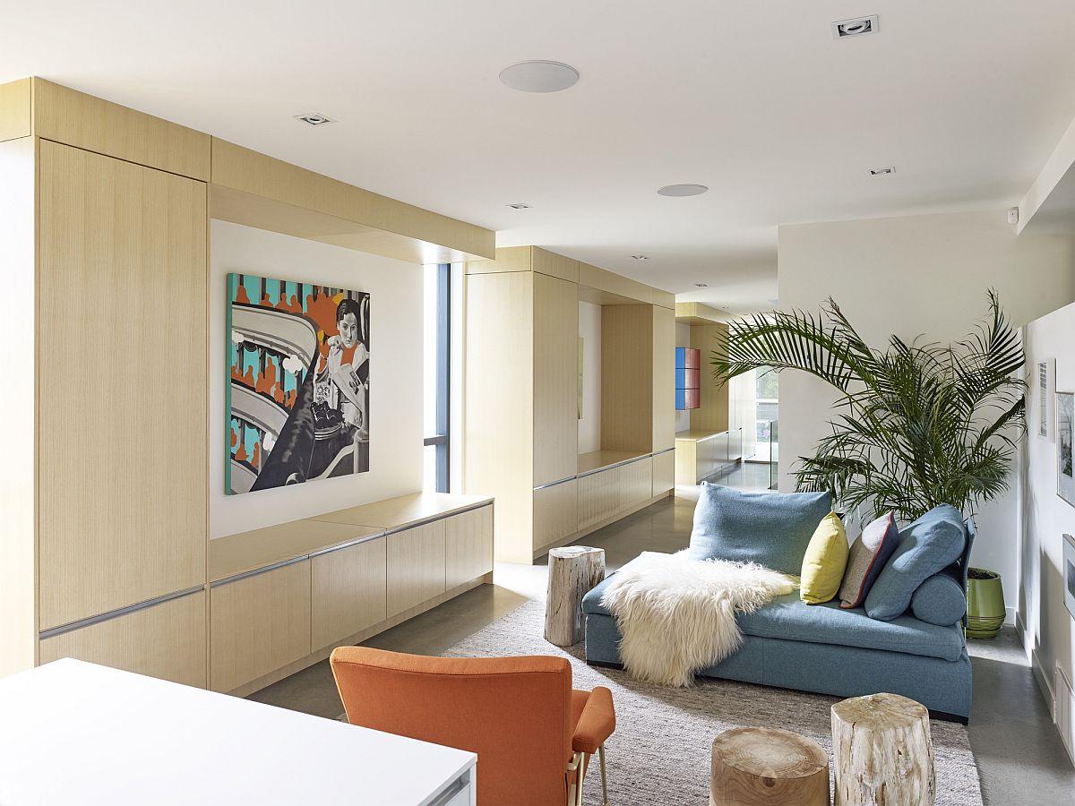 Hình ảnh phòng khách nhà ven sông với sofa xanh dương, ghế bành màu cam, cạnh đó là tranh treo tường màu sắc.