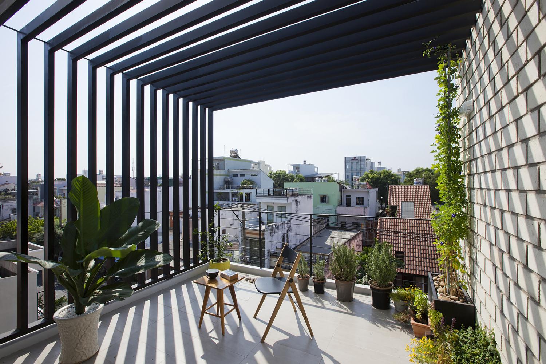 Hình ảnh sân thượng với góc ngồi thư giãn, xung quanh đặt nhiều chậu cây cảnh