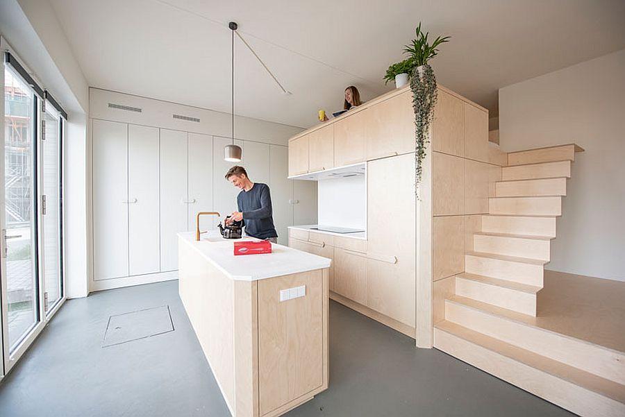 Hình ảnh toàn cảnh không gian sinh hoạt trong căn hộ 45m2 với hệ tủ gỗ màu trắng âm tường, đảo bếp trung tâm, gác xép ngủn nghỉ