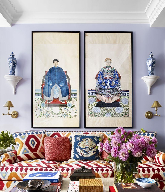 Hình ảnh một góc phòng khách với màu sơn xám lông mèo, tranh treo cổ điển, ghế sofa màu sắc nổi bật