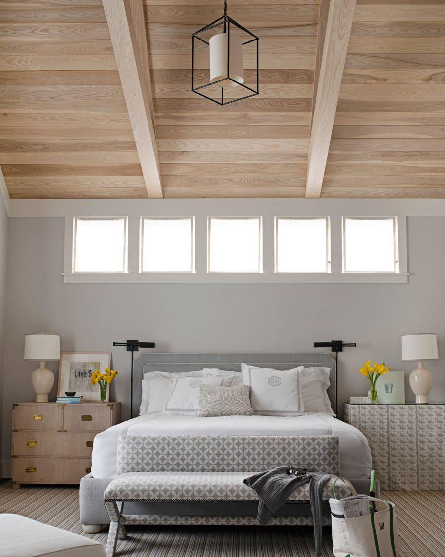 Hình ảnh phòng ngủ màu xám nhạt với trần ốp gỗ, nhiều ô cửa sổ kính đầu giường, đèn trang trí, hai bên giường là tủ đựng đồ