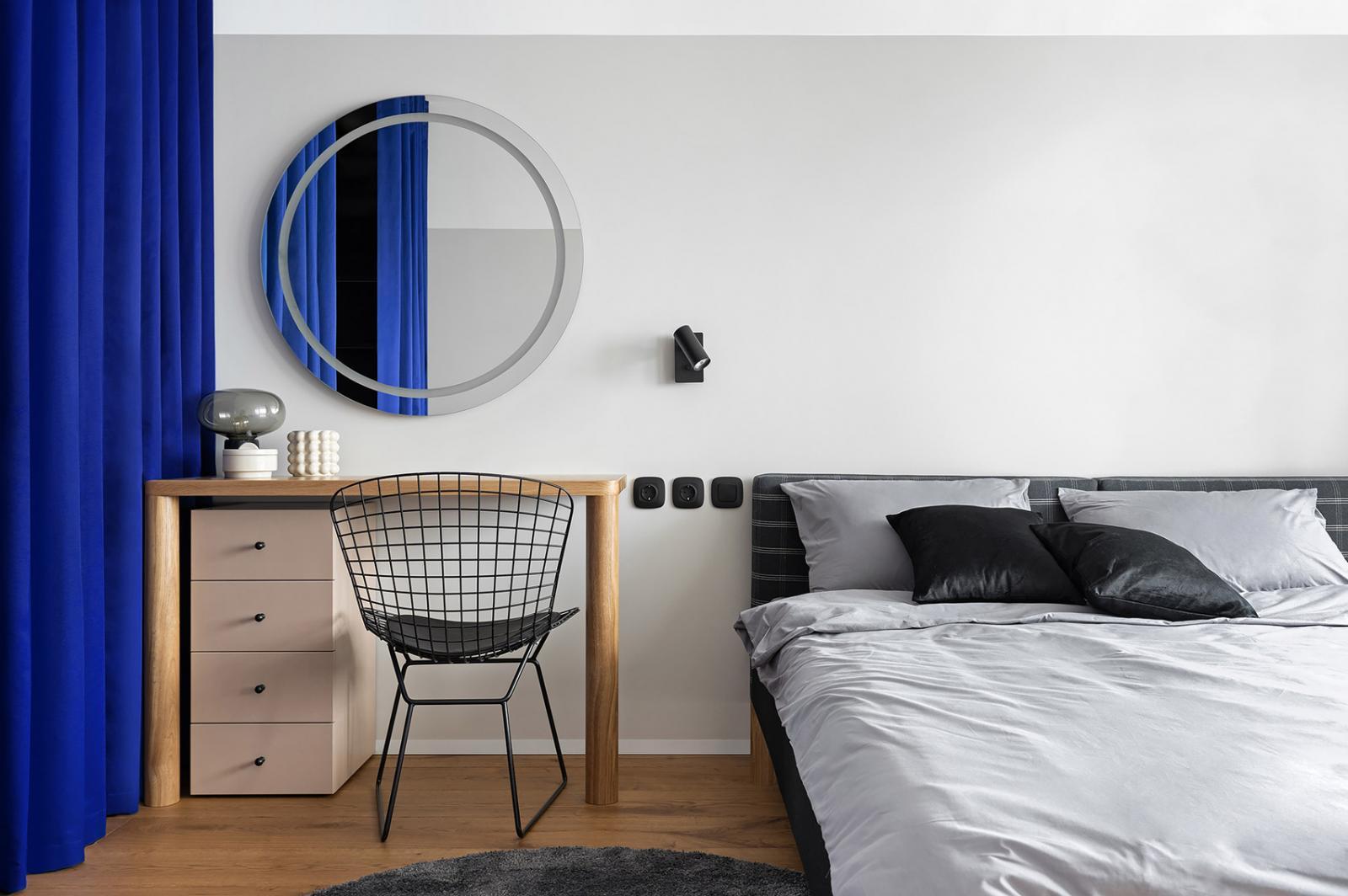 Hình ảnh phòng ngủ với giường nệm êm ái, bàn trang điểm gỗ sồi, tủ ngăn kéo màu hồng, gương tròn, cạnh đó là rèm cửa màu xanh coban