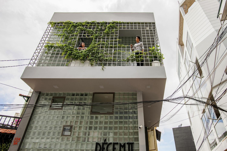 Hình ảnh cận cảnh mặt tiền tầng 2 nhà gạch kính với cây leo xanh mướt, hai người đang đứng ngắm cảnh, chuyện trò