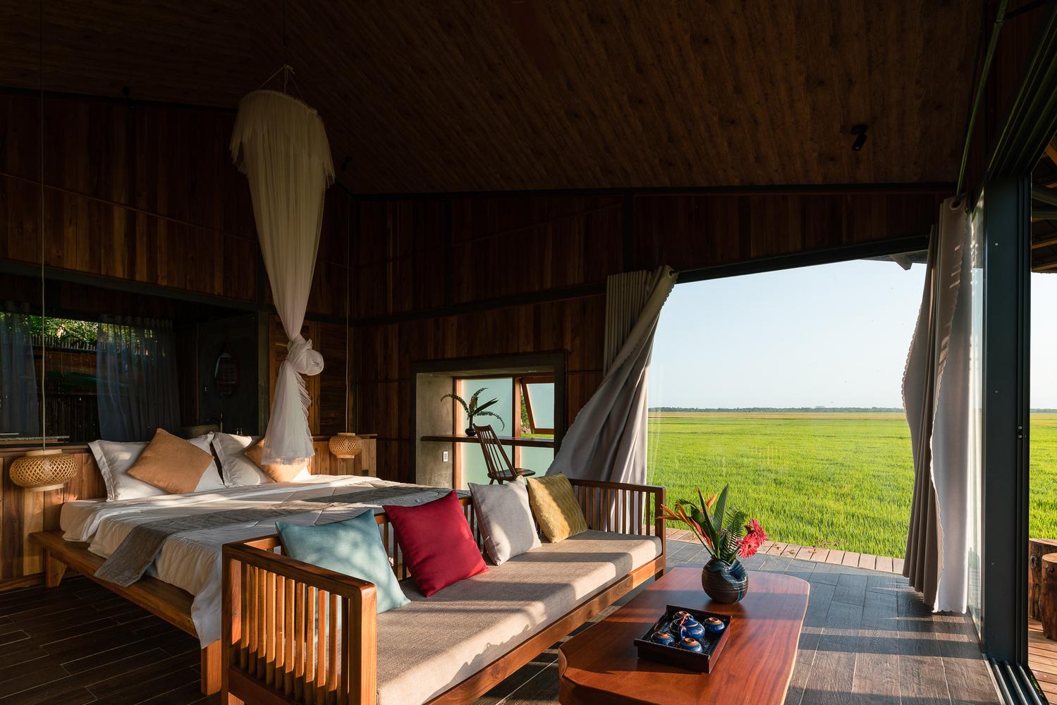 Hình ảnh bên trong nhà nghỉ dưỡng với phòng ngủ tối giản, thoáng sáng, view đồng lúa