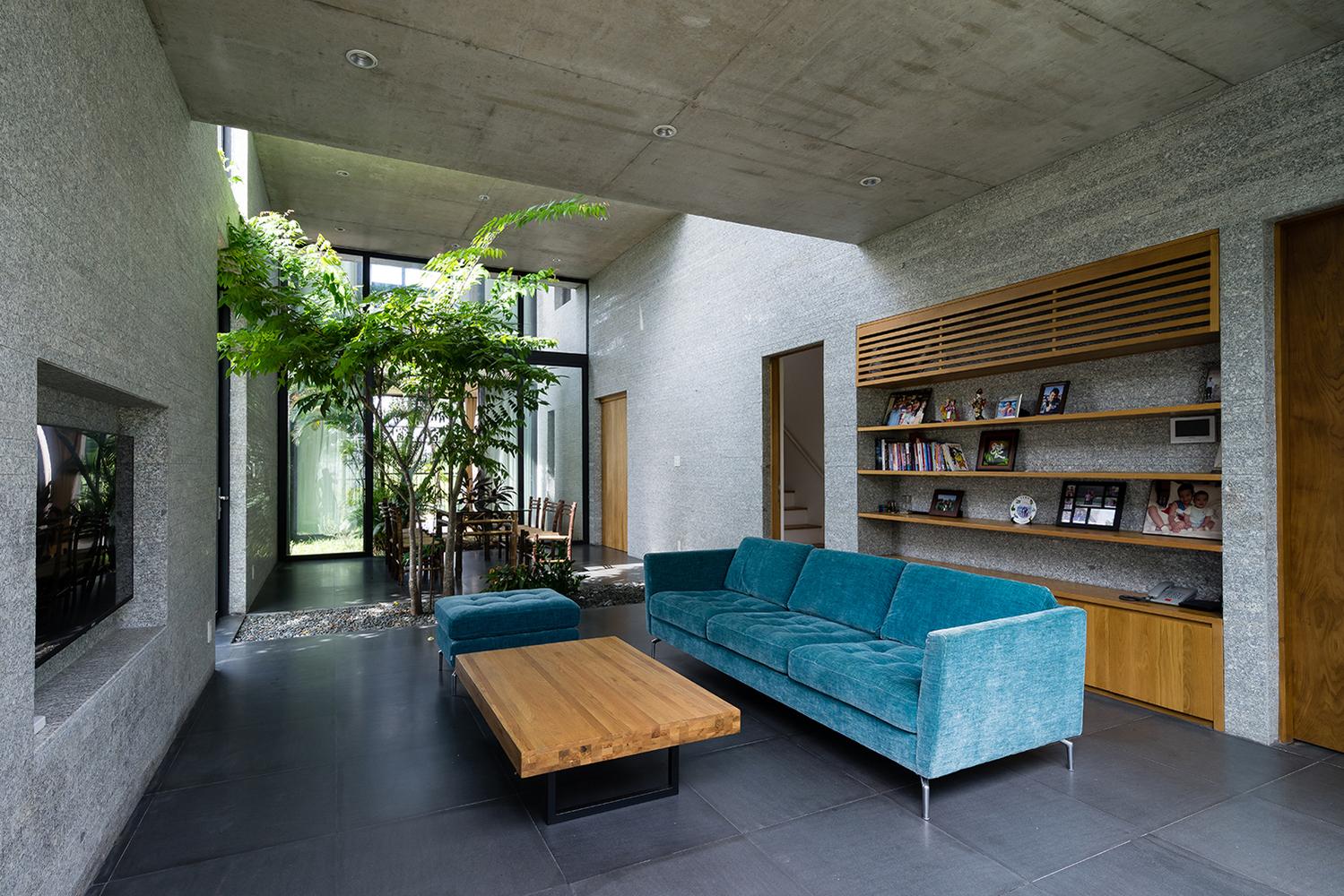 Hình ảnh phòng khách nhà Sài Gòn với bộ sofa màu xanh da trời, bàn trà gỗ, kệ tivi âm tường, kệ mở phía sau ghế sofa