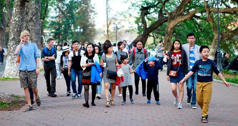 Hình ảnh đoàn du khách đi bộ trên con đường lát gạch quanh hồ Gươm, Hà Nội.