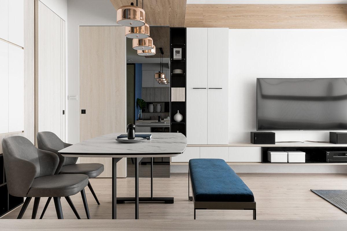 Hình ảnh phòng ăn với bàn mặt đá cẩm thạch trắng, 2 ghế xám, băng ghế dài màu xanh, đèn thả mạ đồng