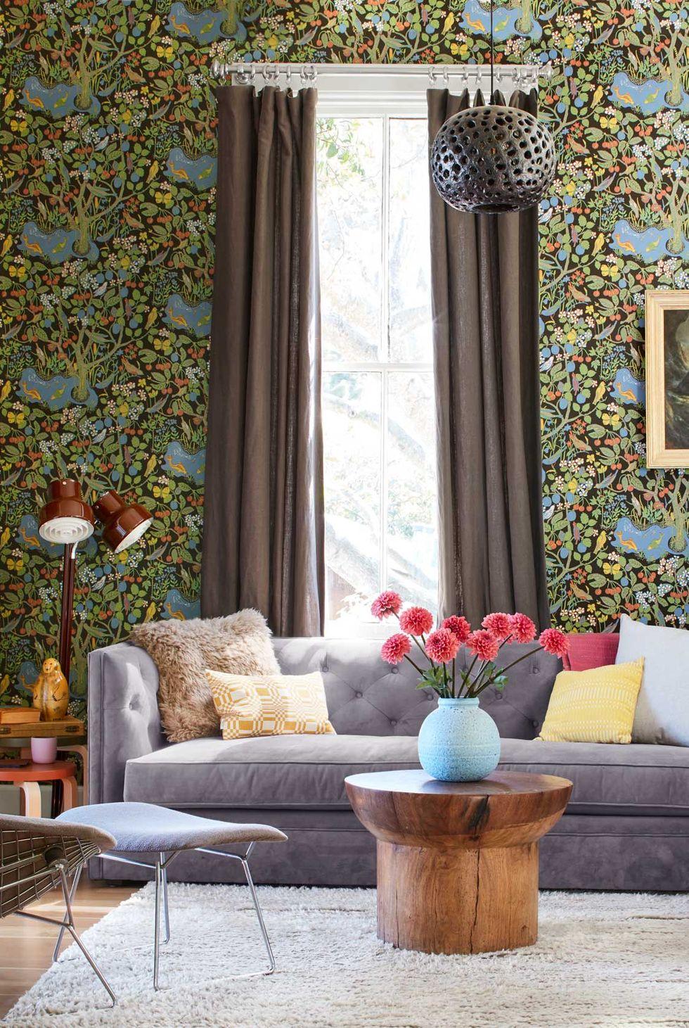 Hình ảnh một góc phòng khách nhỏ với rèm cửa màu nâu dài sát sàn nhà, giấy dán tường họa tiết bắt mắt