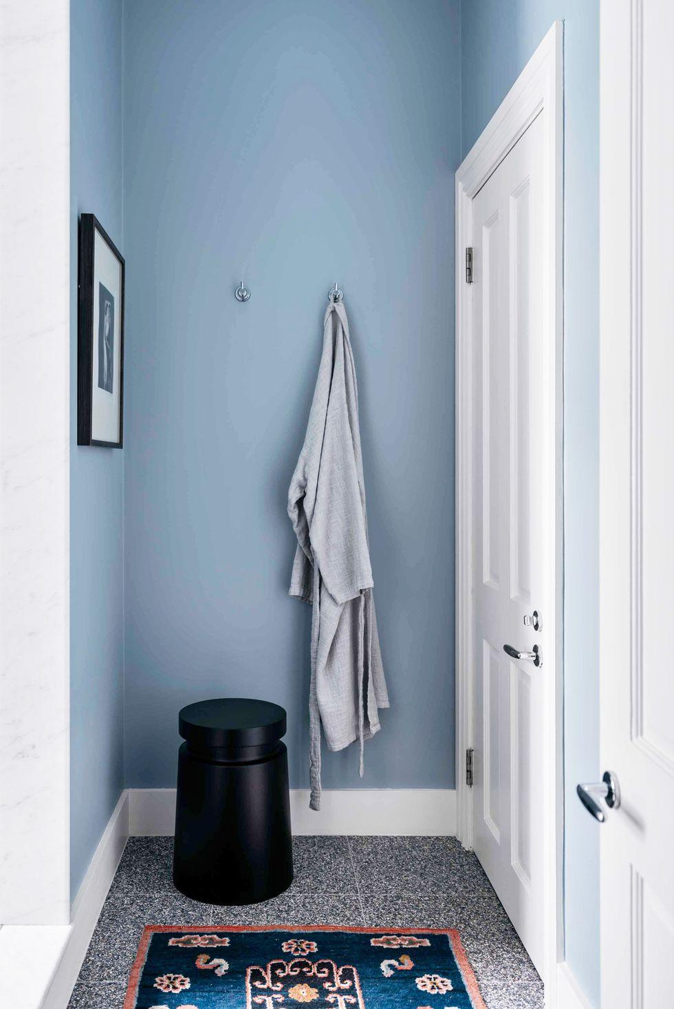 Hình ảnh phòng tắm nhỏ sơn màu xanh da trời, thảm trải họa tiết thổ cẩm cầu kỳ