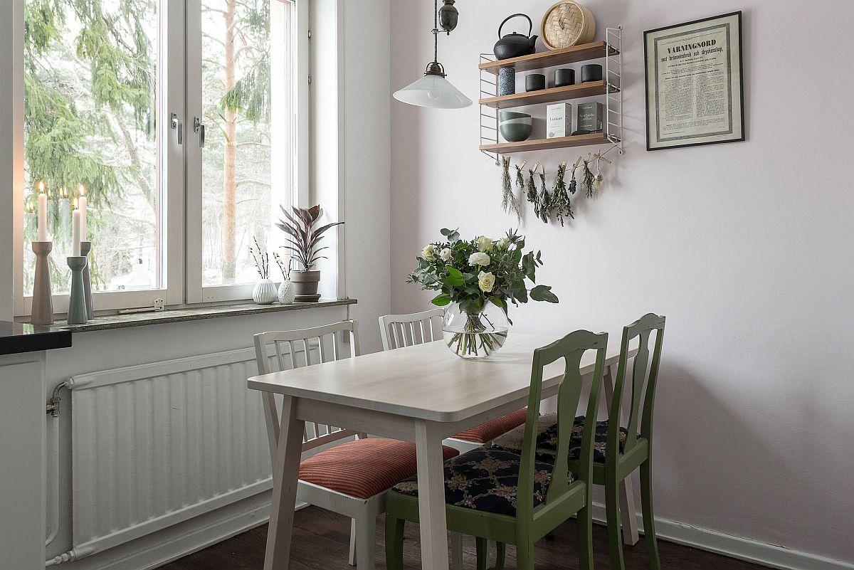 Hình ảnh phòng ăn nhỏ với ghế ngồi màu xanh lá tạo điểm nhấn, cạnh đó là cửa sổ kính thoáng sáng, cây hoa trang trí