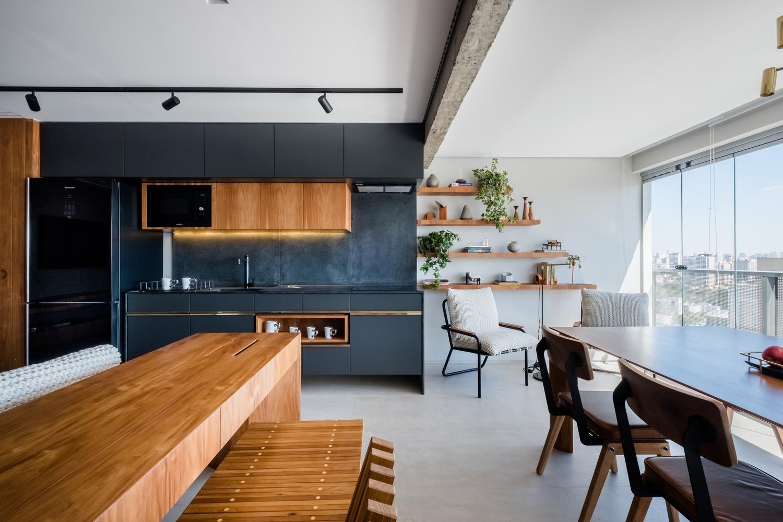 Hình ảnh toàn cảnh phòng bếp ăn với hệ tủ lưu trữ màu xanh than, bàn gỗ, bàn ghế ăn
