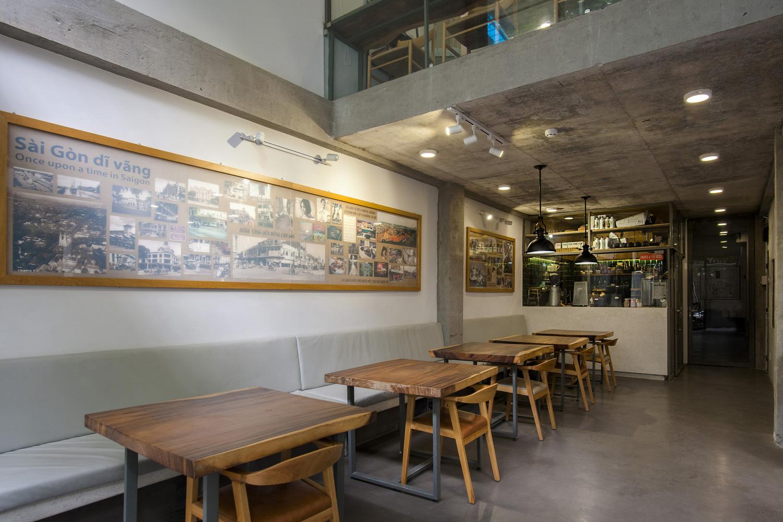 Hình ảnh bên trong một quán cà phê với bàn ghế gỗ, băng ghế dài sát tường, tranh ảnh Sài Gòn xưa, đèn thả trần độc đáo