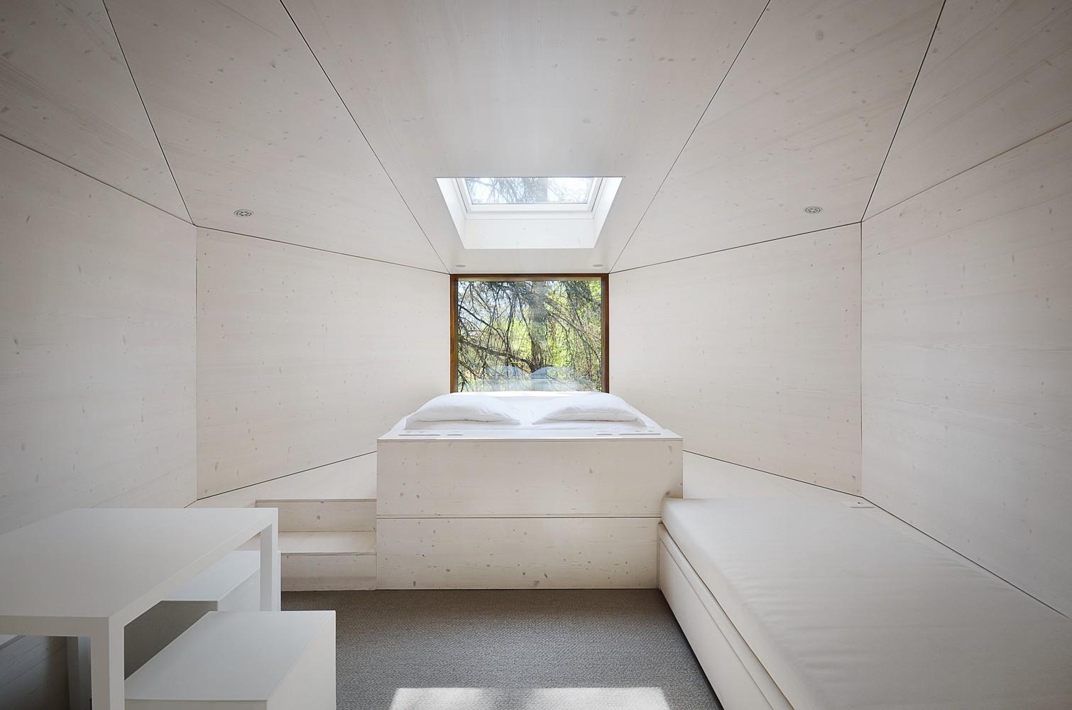 Hình ảnh toàn cảnh không gian sinh hoạt bên trong nhà cabin với phòng khách, bàn ăn, phòng ngủ tông màu trắng chủ đạo